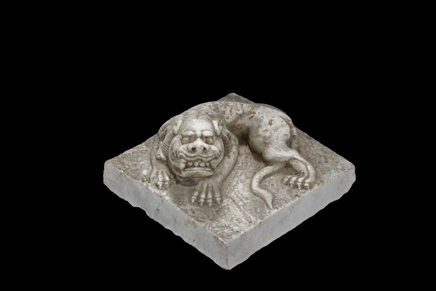 A MARBLE CARVED RECUMBENT LION FIGURE
