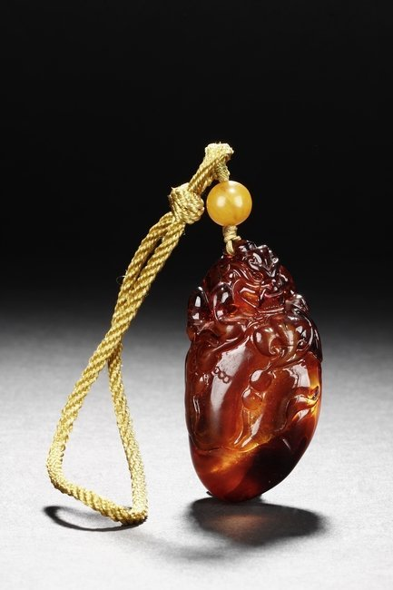 """A CARVED AMBER """"MYTHICAL BEAST"""" ORNAMENT"""