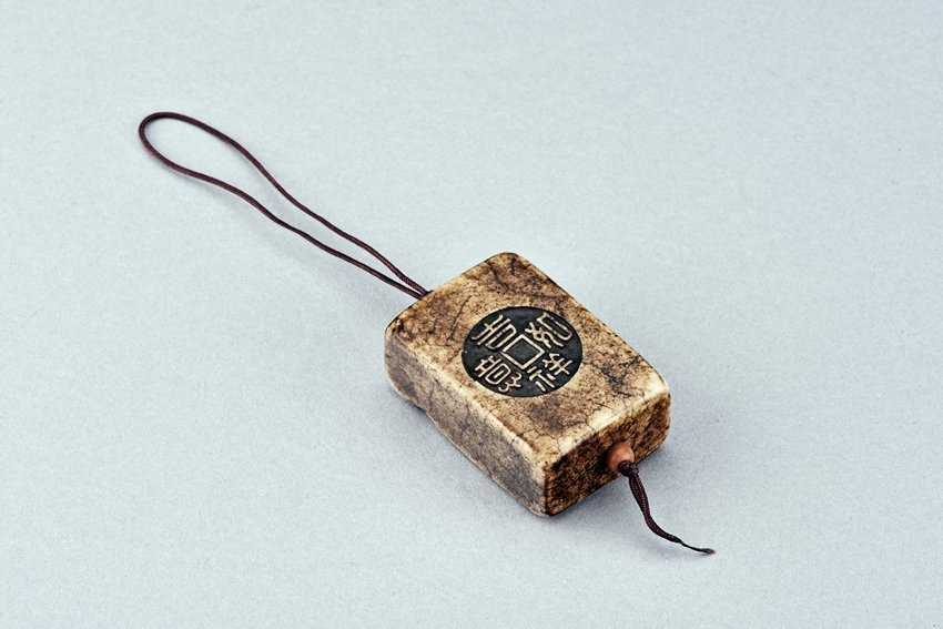 A STONE CARVED 'BAGUA' PENDANT