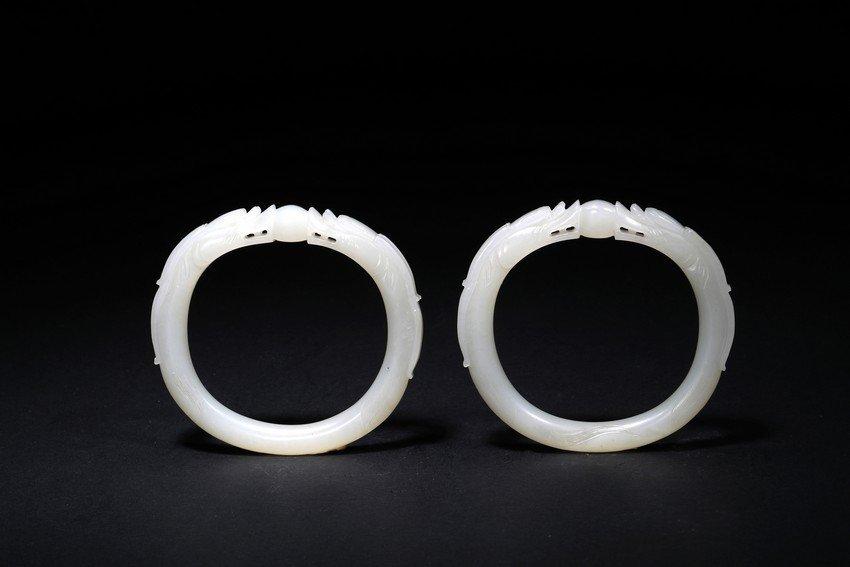 A PAIR OF WHITE JADE DRAGON BRACELETS