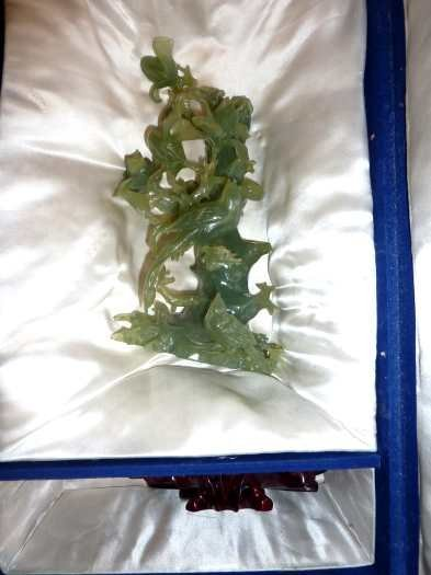 287: Cased Chinese carved green jade figure of various