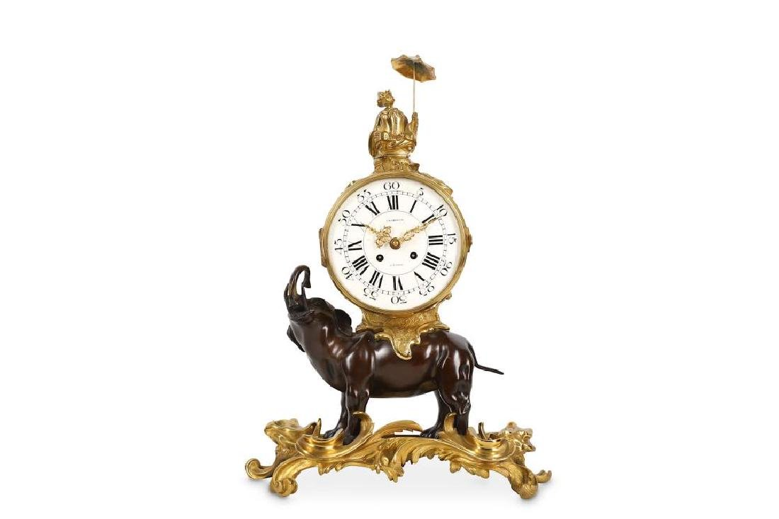 A LOUIS XV STYLE GILT AND PATINATED BRONZE MANTEL CLOCK