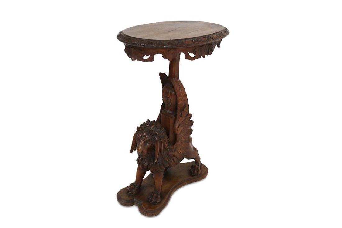 A 19TH CENTURY CARVED OAK OCCASIONAL TABLE MODELLED AS