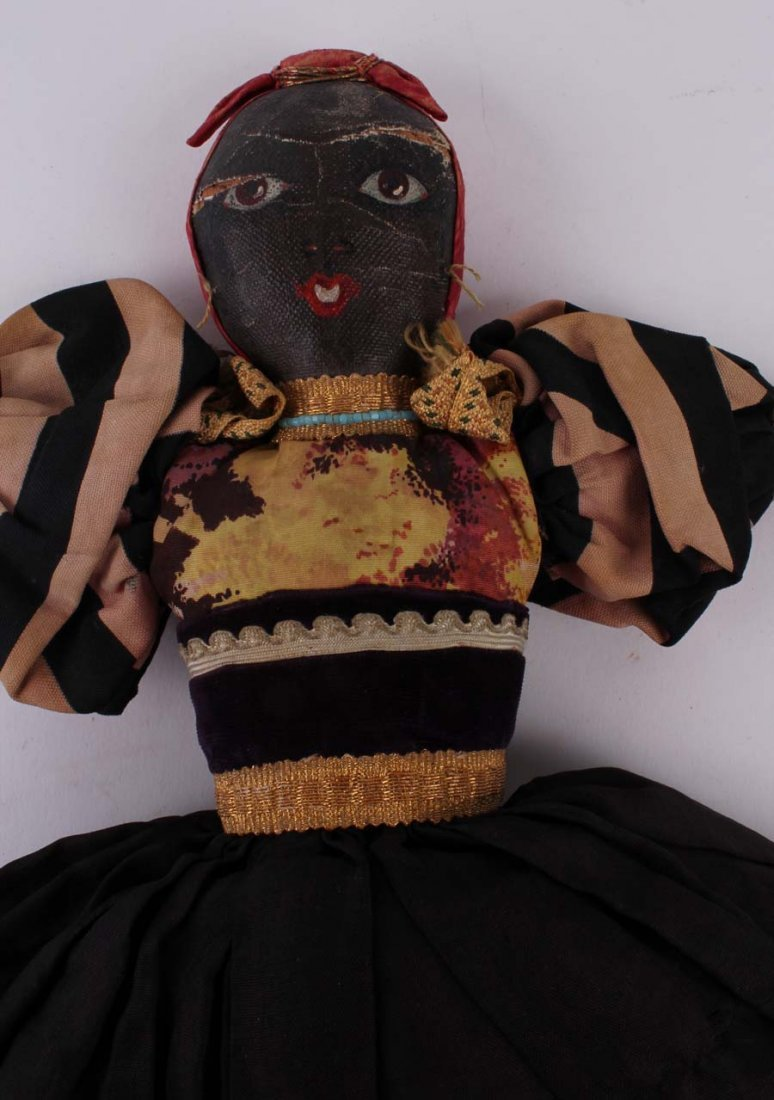 20: An oil painted Topsy Turvy cloth doll, with one sid