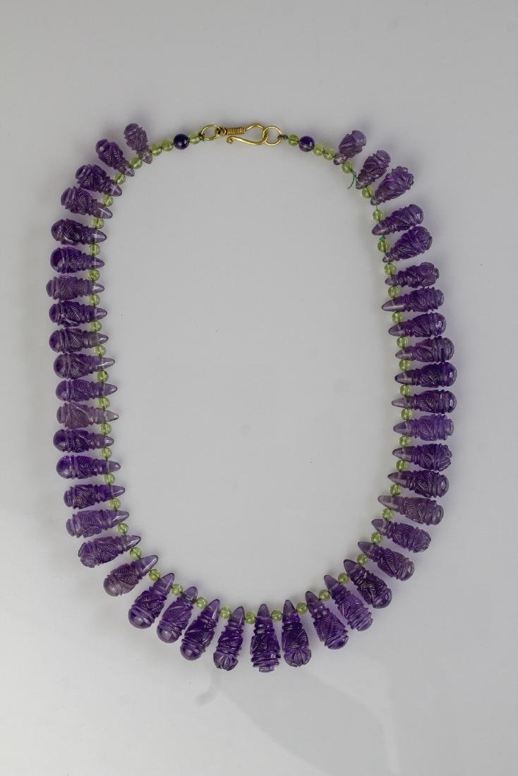 Carved amethysts and peridot necklace, gr 63.40, with