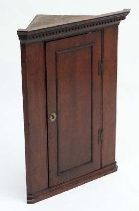 A c.1800 oak hanging corner cupboard 33 1/2'' high