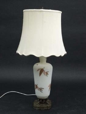 A handed painted white satin glass table lamp with a