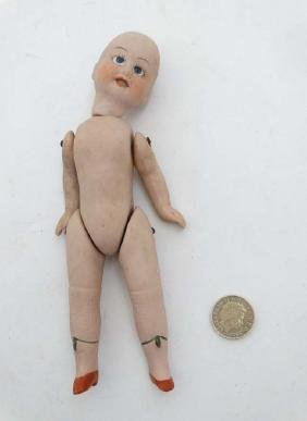 Toy: A small bisque jointed doll , having blue glass