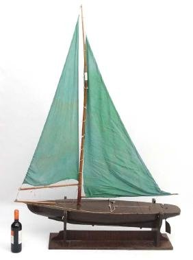 A large Bermuda rigged pond yacht, having hollow wooden