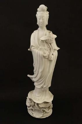 A Chinese Blanc de Chine figure of Guanyin, holding a