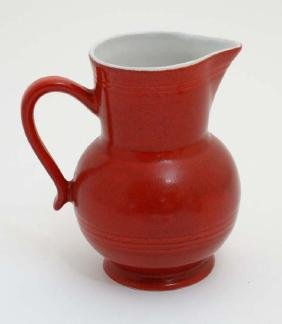 A French Emile Henry red pitcher with white interior,