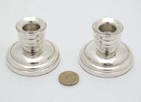 A pair of short silver candlesticks hallmarked