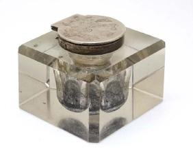 A glass inkwell of squared form with silver hinged lid