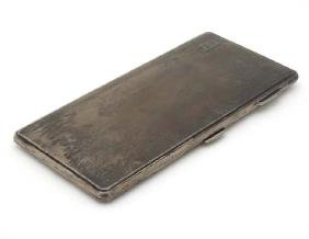 An Art Deco large cigarette case with engine turned