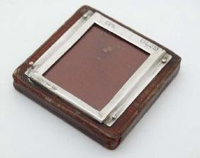 A desk top leather covered paperweight with silver