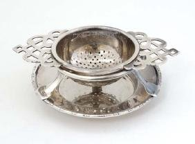 A silver plate tea strainer on stand. 4 1/2'' wide