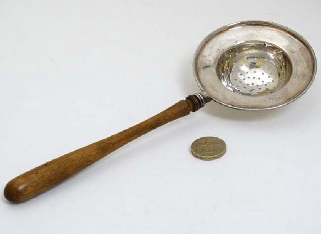 A silver strainer with turned wooden handle. Hallmarked - 3