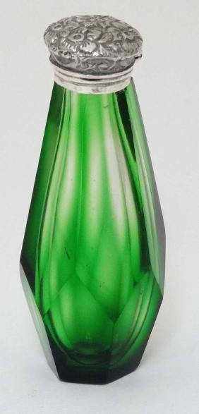 A green glass scent bottle with white metal top. late