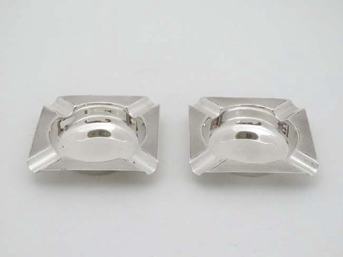 A pair of Art Deco silver ashtrays with engine turned