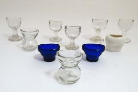 9 assorted glass eye baths together with a ceramic