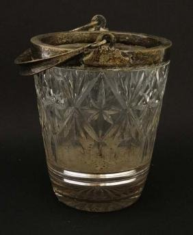 A cut glass ice bucket with silver plated mounts and