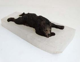 A cast bronze model of a recumbent bear on a rock