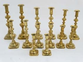 Assorted brass candlesticks, some with plungers. The