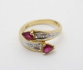 A 14k gold ring set with rubies and diamonds