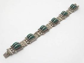 A Mexican silver bracelet set with green silver
