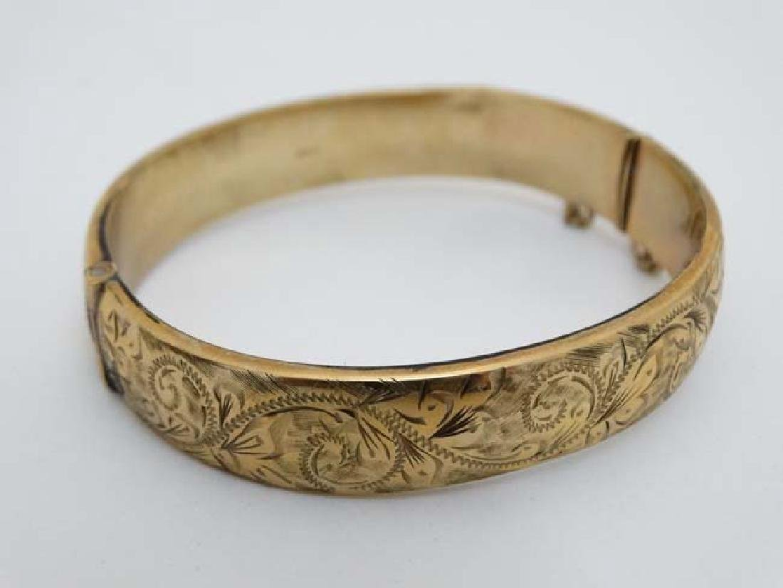 A 9ct gold bracelet of bangle form  with engraved