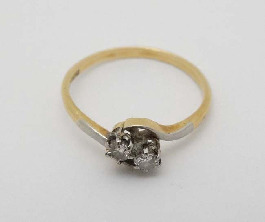 An 18ct ct gold ring set with two diamonds to top