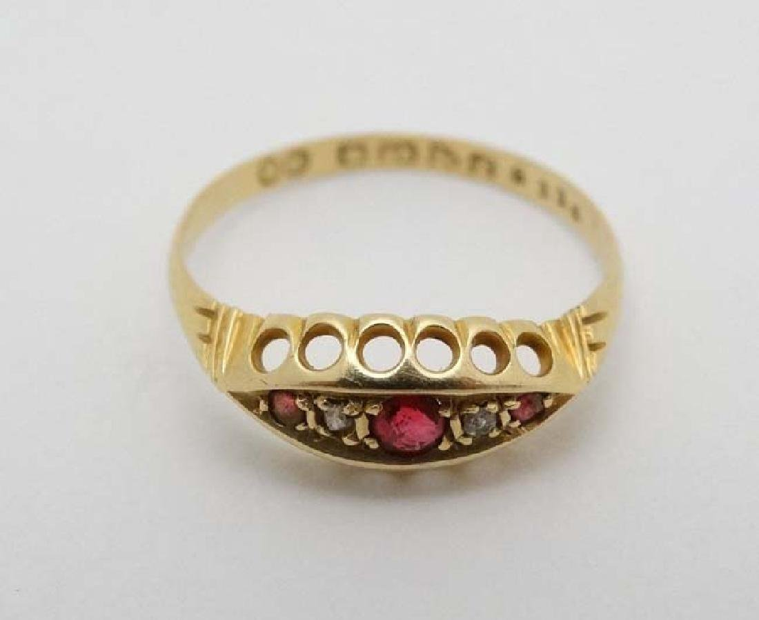 An 18ct gold ring set with diamonds and red stones.