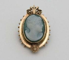 A cameo brooch set with green and white cameo within a