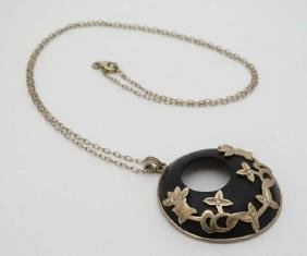 A silver gilt chain with ebony pendant with silver gilt