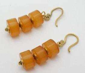 A pair of yellow metal drop earrings set with amber