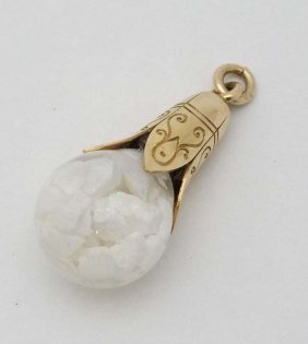 A gilt metal pendant with glass sphere containing opal