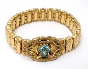 A gold plated expanding bracelet with aqua blue stone