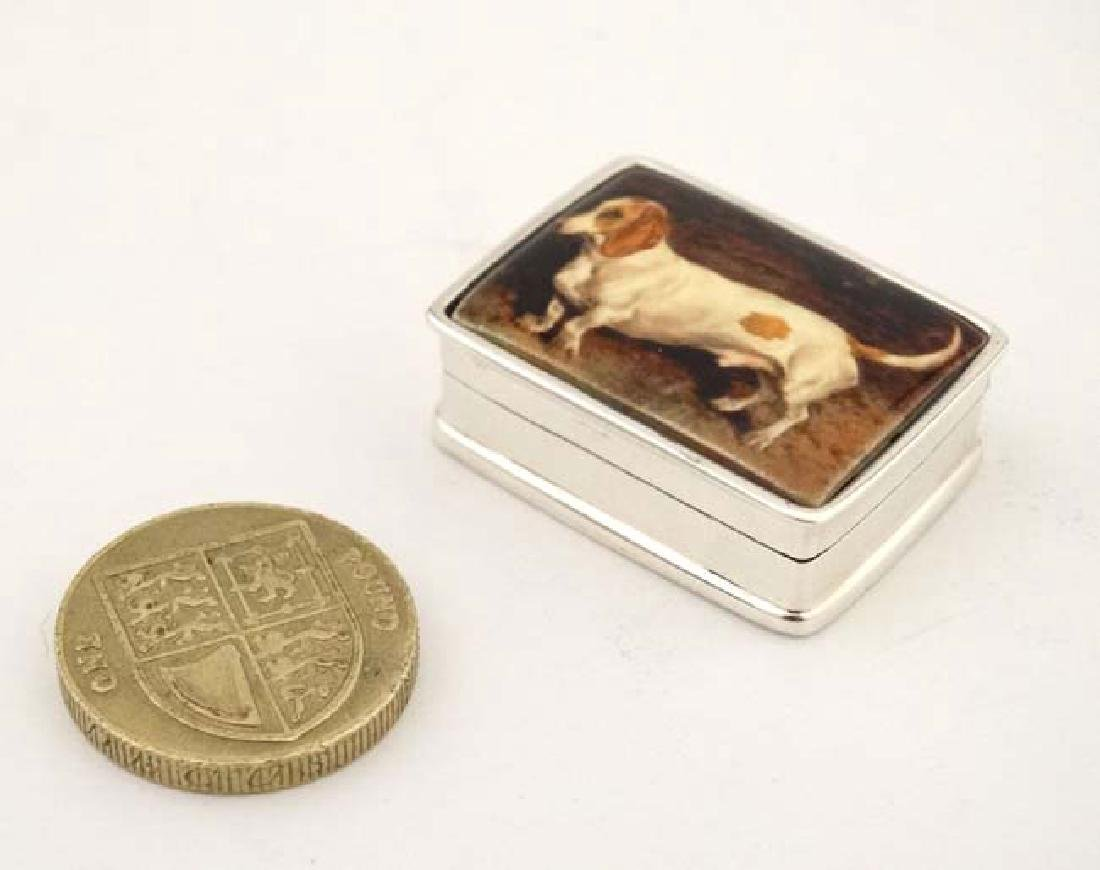 A .925 silver pill box with hinged lid depicting enamel