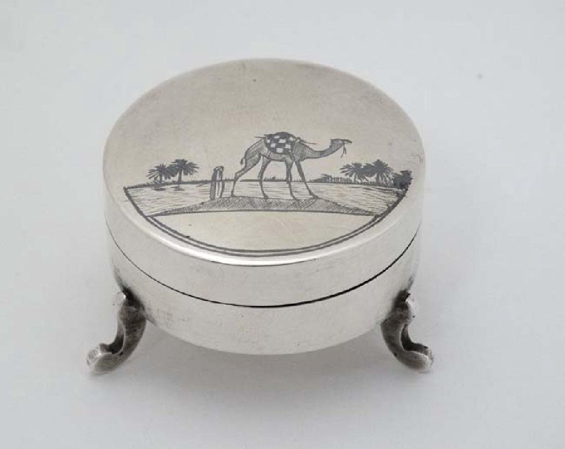 A white metal pot and cover on three shaped feet and