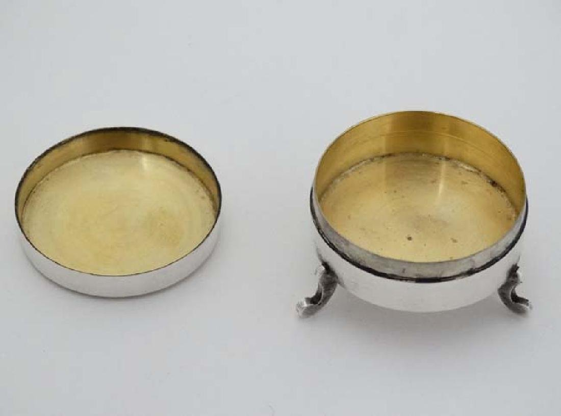 A white metal pot and cover on three shaped feet and - 5