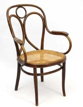 A Thonet bentwood open armchair with caned seat and