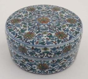 A Chinese circular lidded pot. Hand painted with floral