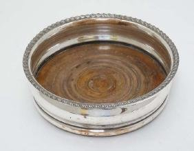 A silver plate coaster with turned wooden base. 5 3/4''