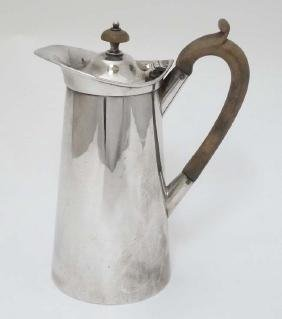 A silver plated coffee pot with wooden handle and