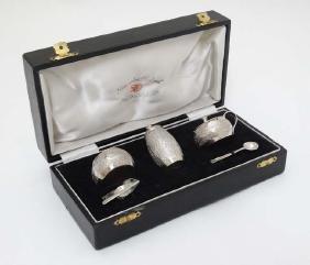 A white metal cruet set comprising salt pepper and