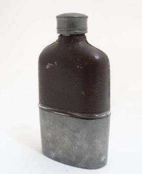 A hip flask with half leather covering and beaker to
