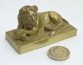 An early 19thC gilt bronze cast lion on squared socle.