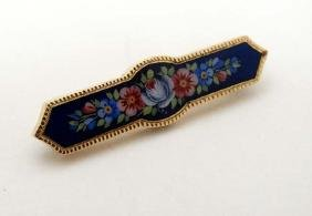 A yellow metal brooch with floral enamel decoration to