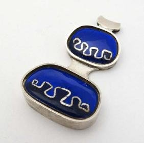 A modernist silver pedant with blue enamel decoration.