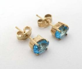 A pair of yellow metal stud earrings set with topaz